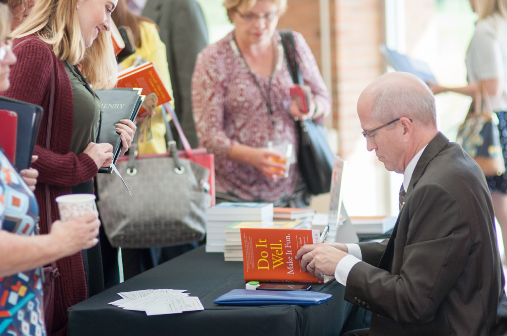 Funny speaker Ron Culberson signs books at a conference.